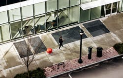 Overhead image of man walking along Atlanta sidewalk with gita the following robot in signal red