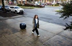 Woman walks along Seattle sidewalk with gita the following robot in twilight blue