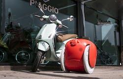 Signal red gita robot parked outside a Piaggio store next to a Vespa Primavera